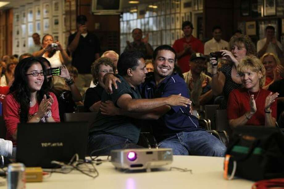 Rice infielder Anthony Rendon is hugged by his father Rene next to his mother Bridget (right) and girlfriend Amanda Rodriguez (left) after Rendon was selected sixth in the first round of the MLB draft by the Washington Nationals on Monday during a draft watch party at Rice Stadium. Photo: Johnny Hanson, Chronicle