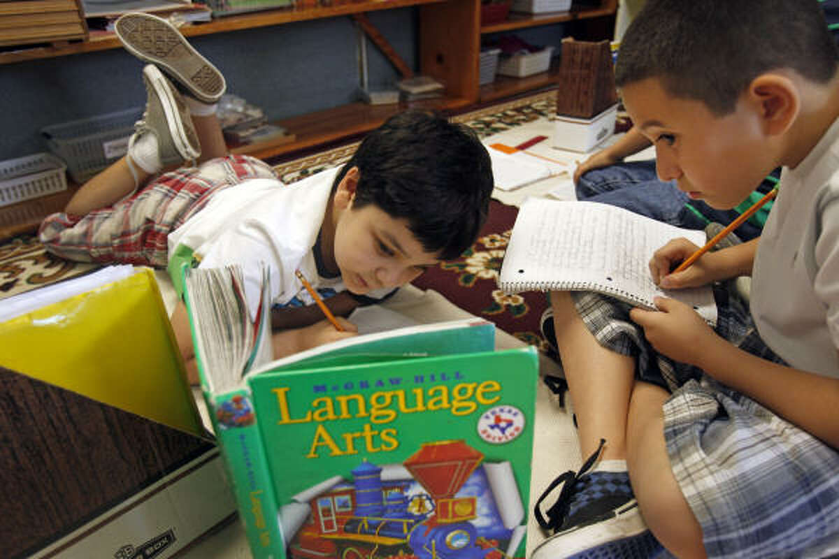 Diego Patron, left, and Michael Martinez, both 9, work on a punctuation lesson at Alief Montessori Community School. Of the top 10 local elementary schools, the school has one of the lowest per-pupil spending amounts, according to state data.