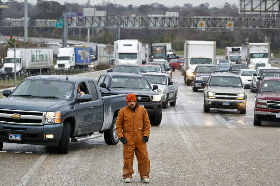 A state highway worker looks over the snarled traffic on I-45 southbound near Quitman on Friday. Photo: Michael Paulsen, Chronicle