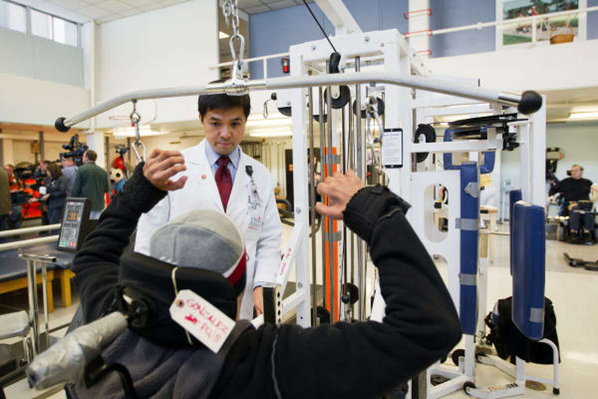 Dr. Gerard Francisco, chief medical officer of TIRR Memorial Hermann Rehabilitation Hospital, talks with a patient. U.S. Rep. Gabrielle Giffords' treatment at the facility costs roughly $8,000 a day, out of reach for most patients whose insurers won't pay that price.