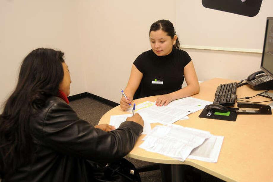 La empleada de la empresa H&R Block Coral Cárdenas (der.) ayuda a preparar la declaración de impuestos de María Arellano en la oficina ubicada en Spencer Highway, Pasadena. Photo: Dave Rossman, Para La Voz