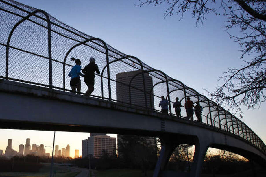 Marathon training partners Erin Logan, left, and Elena Esponza take the Jackson Hill footbridge over Memorial. Photo: Michael Paulsen, Chronicle