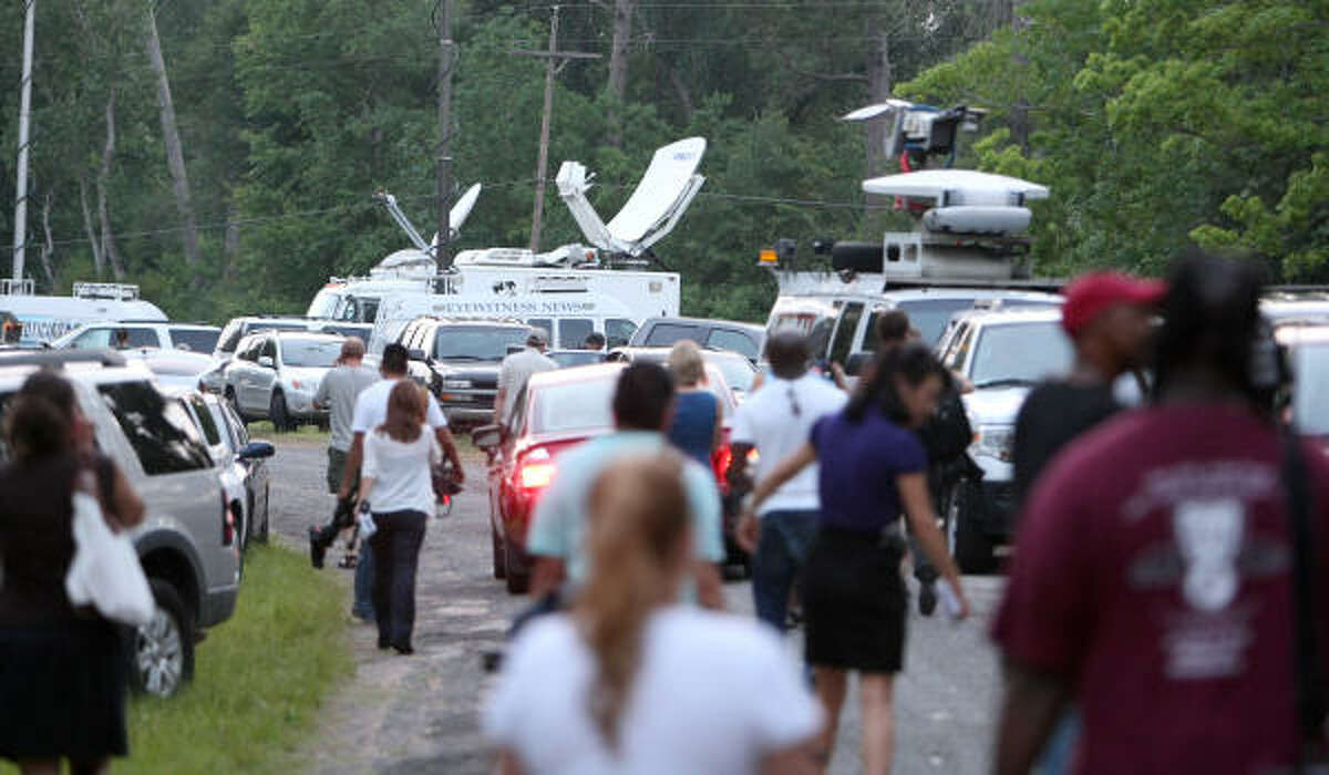 Local and national media return to their vehicles after Capt. Rex Evans of the Liberty County Sheriff's Department said dead bodies weren't found.