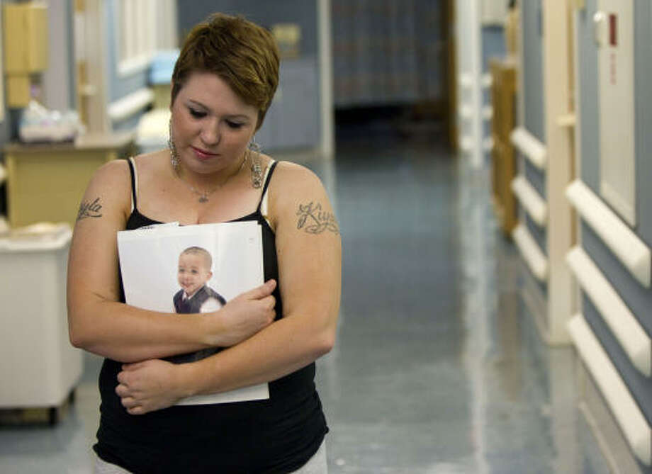 Tiffany Dickerson holds a photo of her son Shomari, who died in the fire, as she waits at Shriners Hospital for Children in Galveston to see her daughter Makayla, who was burned. Photo: Brett Coomer, Houston Chronicle