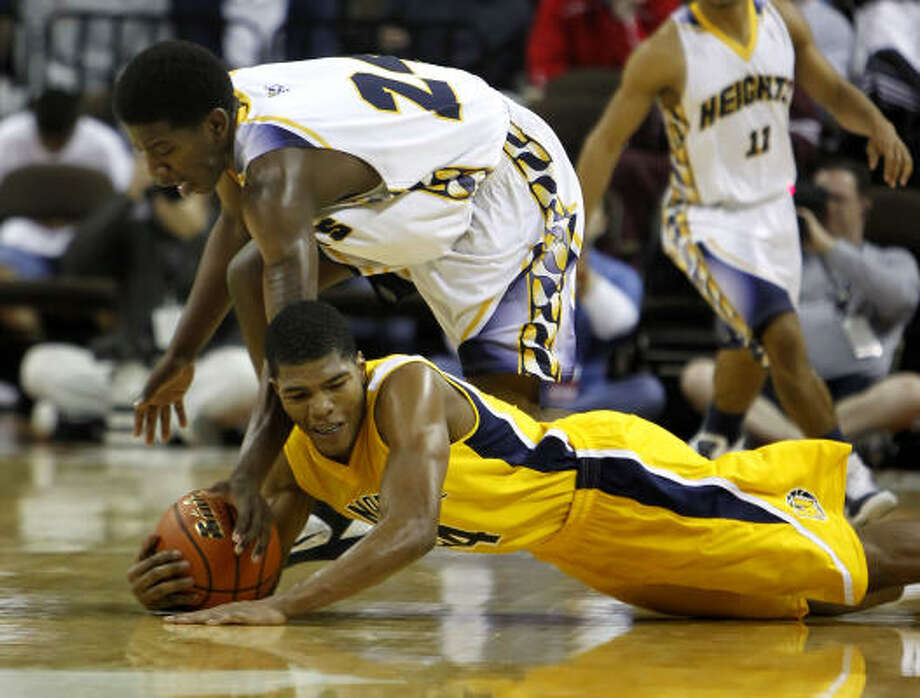 La Marque guard DeQuentin Greer dives in front of Arlington Heights forward Travis Williams for a loose ball. Photo: Erich Schlegel, For The Chronicle
