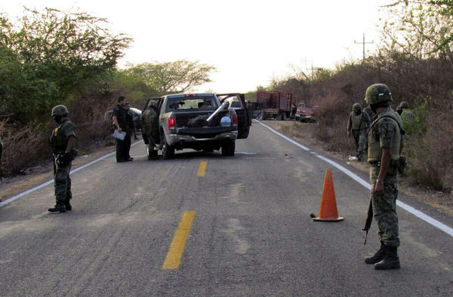 Army soldiers block a road after a gunbattle on Thursday between rival drug gangs near the town of Ruiz, in the Pacific coast state of Nayarit, Mexico. At least 30 men were killed. Photo: Associated Press