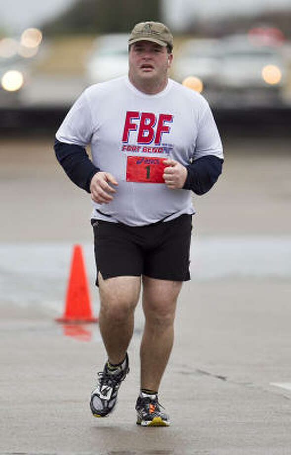 Anthony Antonidis runs in the USA Fit half marathon, Antonidis spent 8 hours grilling chicken sandwiches in freezing weather for marathon participants last year and was inspired to run the half marathon this year. Photo: James Nielsen, Chronicle