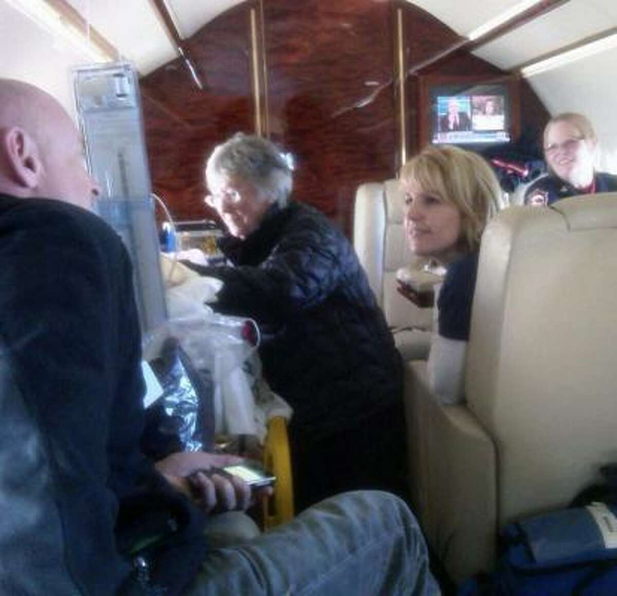 Gloria Giffords, mother of U.S. Rep. Gabrielle Giffords, attends to her Friday on the flight from Tucson to Houston. The congresswoman's husband, astronaut Mark Kelly, left, chats with one of Giffords' nurses, Tracy Culbert.