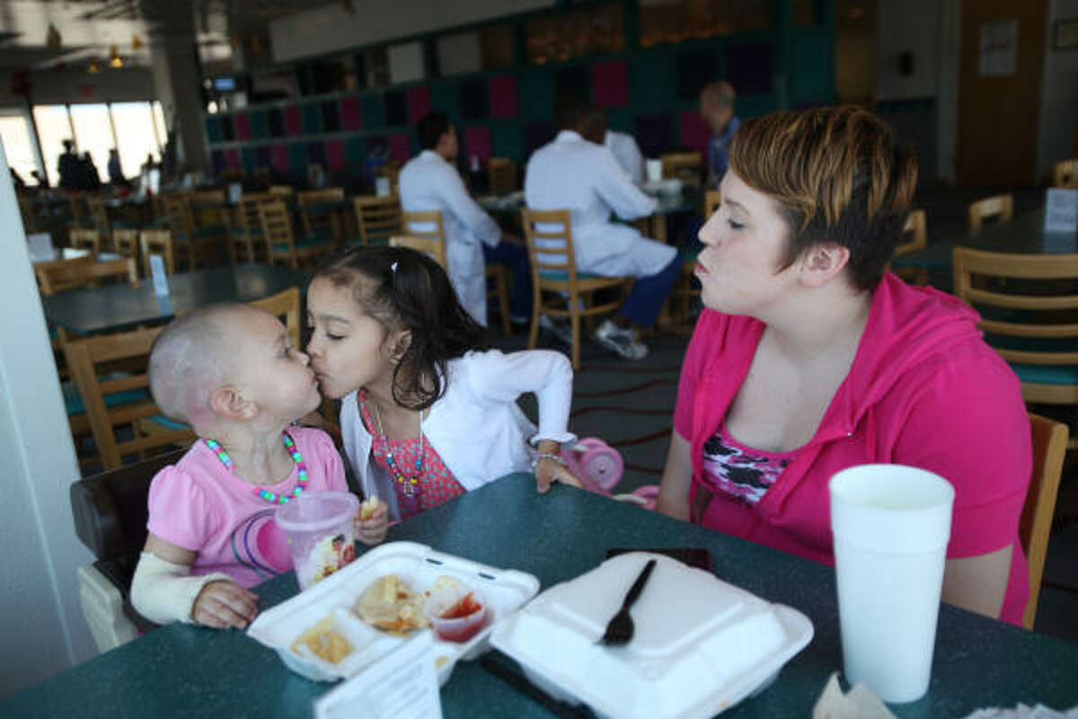 Makayla Dickerson, 2, gets a kiss from big sister Kiyanna Richardson as they eat lunch with their mother at Shriners Hospitals for Children-Galveston on March 21. A certified nursing assistant, Tiffany Dickerson is accustomed to medical surroundings - but not from the perspective of a patient's parent. Her son, Shomari, was one of four child victims of the day care fire. Makayla has spent the past month in Shriners for treatment of extensive burns she suffered in the same fire.