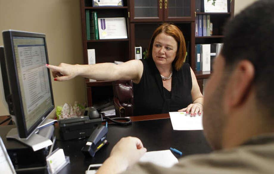 H&R Block manager Marian Clarke shows Alex Galvan this week what he will be getting back on his taxes at a Sugar Land H&R Block branch. The deadline for filing income taxes this year is Monday. Photo: Cody Duty:, Chronicle