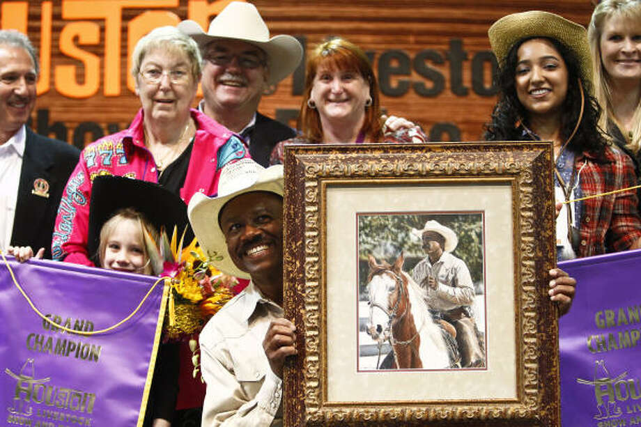 Larry Callies holds Kimberly Agarwal's (second from right) Grand Champion painting, which fetched $205,000 by a group of four buyers during the 16th annual School Art Auction at the Houston Livestock Show and Rodeo on Sunday. Photo: Michael Paulsen, Chronicle