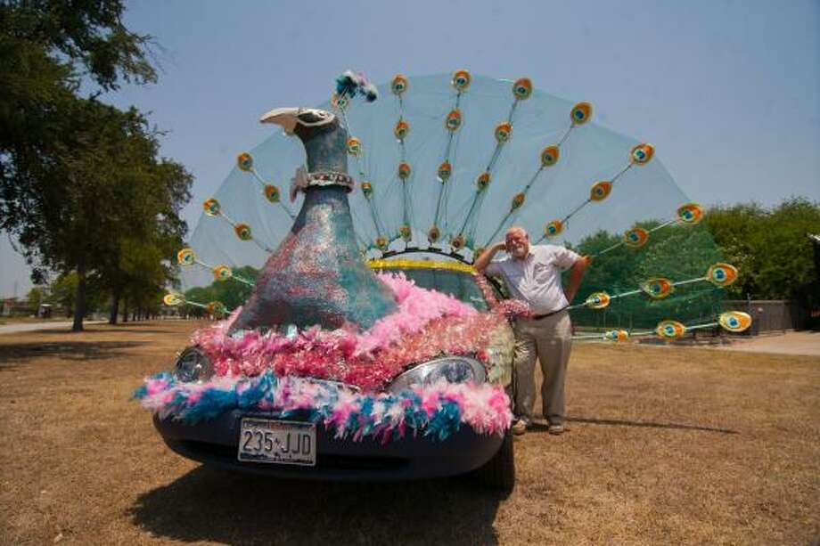 """TAKING PRIDE: Mark Garrett of Jersey Village poses with """"Percy the Peacock"""" outside the Art Car Museum. The peacock-mobile followed the mayor's car this year in the 24th annual Art Car Parade on Allen Parkway. Photo: R. Clayton McKee, For The Chronicle"""
