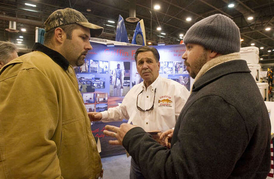 Raymond Griffin, center, with Griffin Fishing & Lodging, has been at the Houston Boat show trying to lure attendees like Louis Krolczyk Jr., left, and Brandon Dotter back to the Louisiana coast in the wake of last year's oil spill that closed his business. Photo: James Nielsen, Chronicle