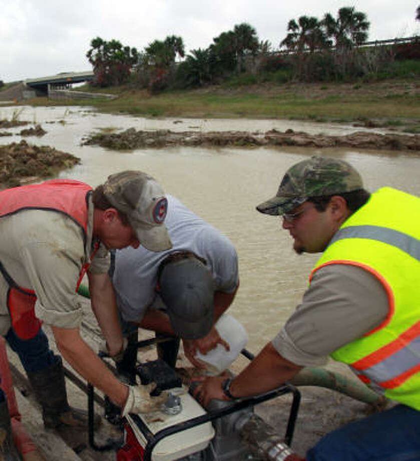Workers with the Gulf Coast Water Authority work to pump out water from an area where a 42-inch water line is damaged. Photo: Johnny Hanson, Chronicle