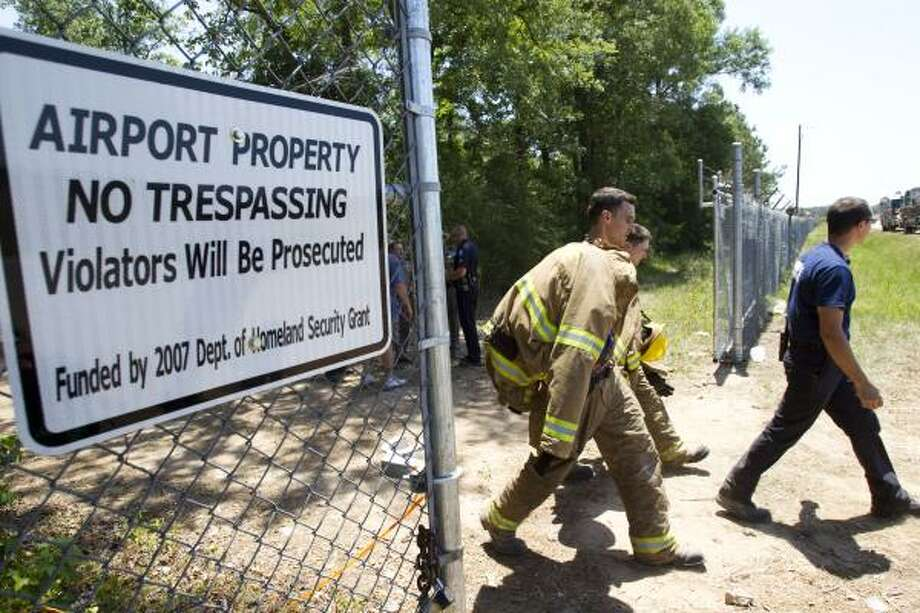 Firefighters leave the site of the crash Saturday near the Montgomery County Executive Airport. State Trooper Erik Burse said an experimental aircraft crashed in the woods north of the runway. Photo: Brett Coomer, Chronicle