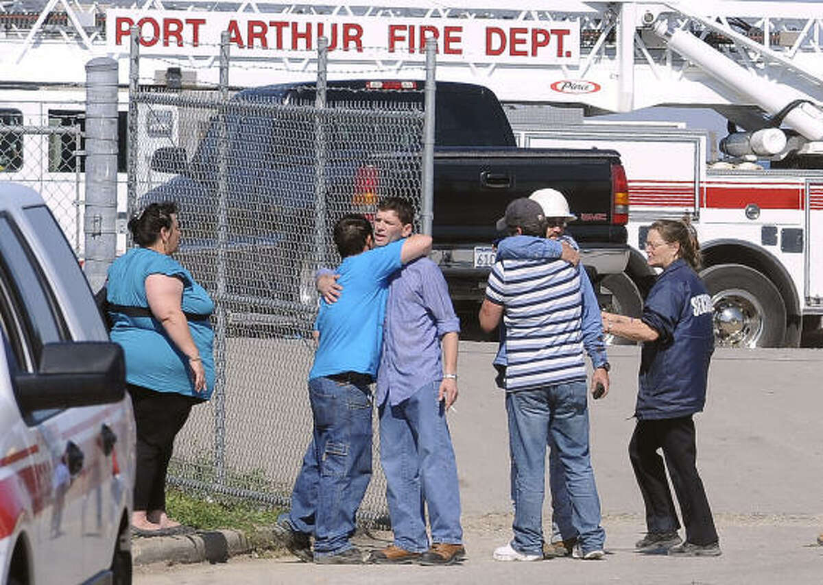 Family members and friends grieve at the front gate of KMTEX chemical facility in Port Arthur after Thursday's flash fire and blast.