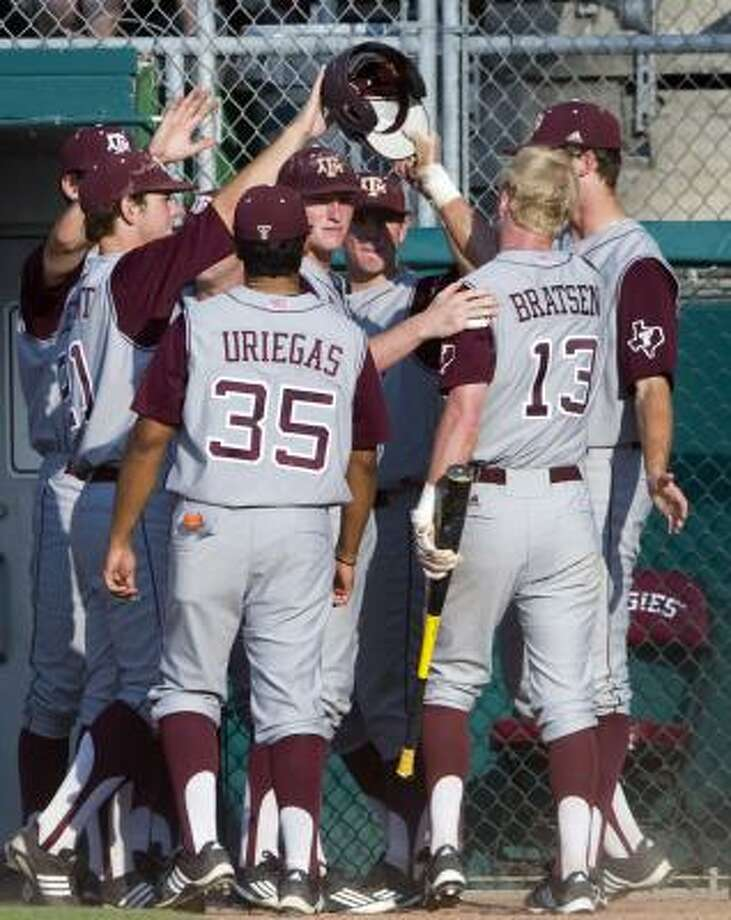 A&M's Krey Bratsen (13) is met by teammates after scoring during the first inning against Seton Hall on Saturday. Photo: Stuart Villanueva, Associated Press