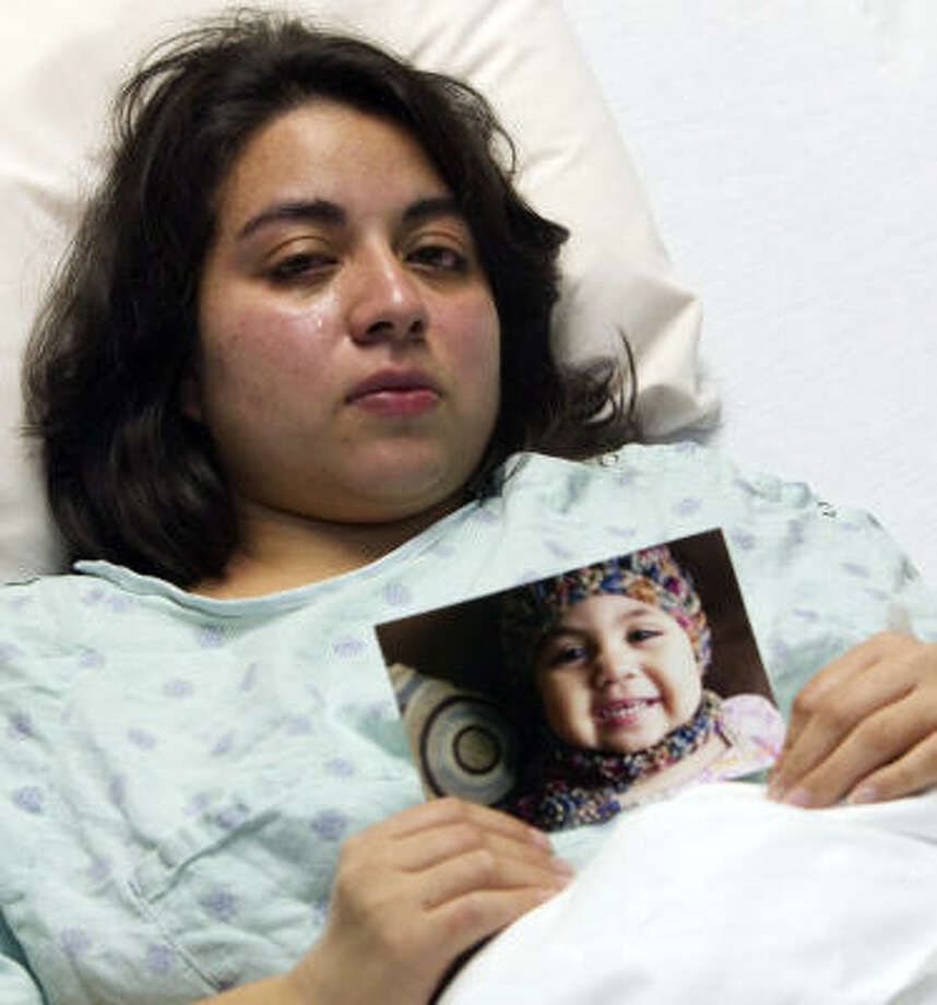 Maria Sanchez holds a photo of her daughter Melissa Aguillon, 3, at Ben Taub General Hospital in Houston last week. A tumor is limiting the use of her arms and legs. Photo: Billy Smith II, Chronicle