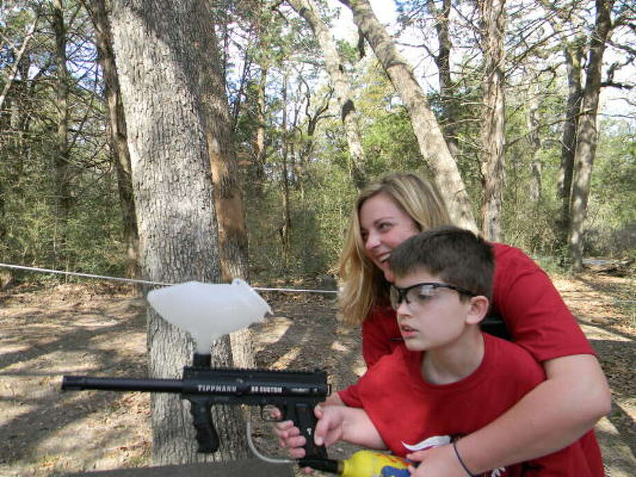 CAMP ROCKS: Garrett Polk takes aim with help from teacher Sally Schwartzel, who helped organize Camp Rocks. Photo: Courtesy, Camp Rocks