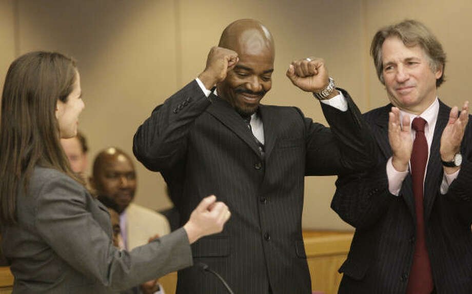 Cornelius Dupree Jr., center, raises his hands in celebration with his lawyer Nina Morrison, left, and attorney Barry Scheck in Dallas on Tuesday, Jan. 4, 2011. Dupree served 30 years for rape and robbery before being exonerated by DNA evidence. Photo: Mike Fuentes, AP