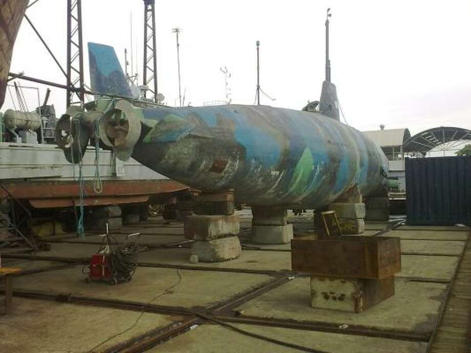 Experts have studied the narco submarine, which sits in Guayaquil, Ecuador. Painted a camouflage pattern of blue, black and gray, it is believed to be able to submerge about 50 feet. Photo: Special To The Chronicle