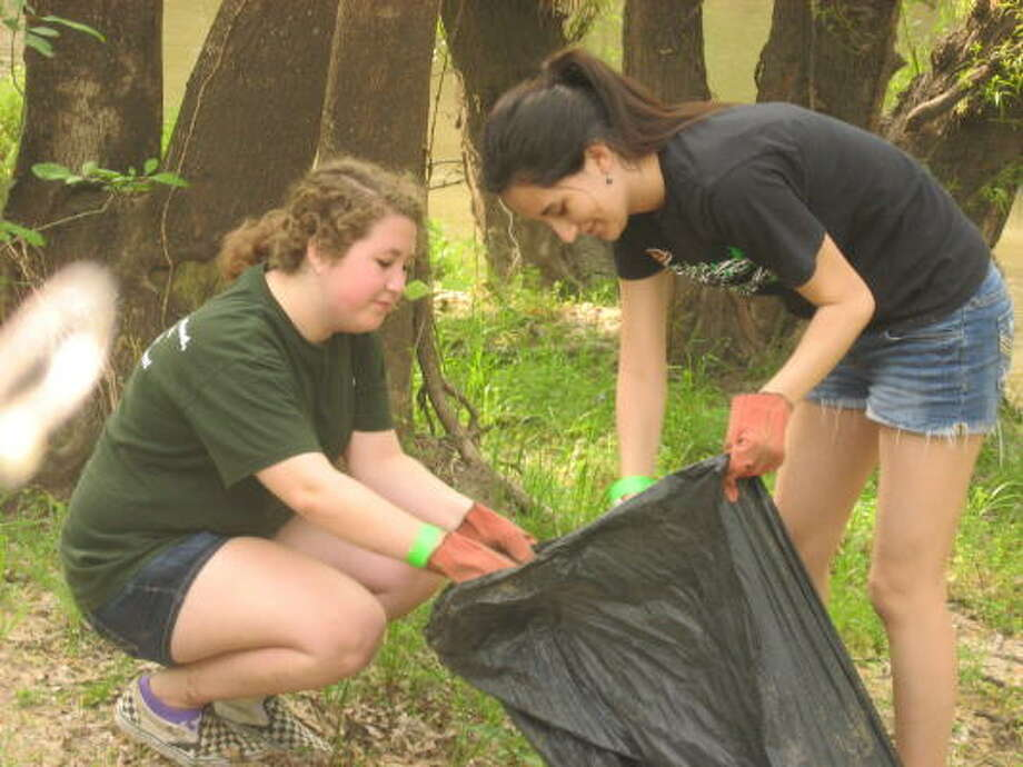COURTESY PHOTO MAKING THINGS BETTER: Mekenna Mortensen, left, and Emily Gonzales of Stratford High School, work on the banks of Buffalo Bayou near Texas 6 removing trash and debris at Trash Bash 2011 at Terry Hershey Park. Photo: ALL