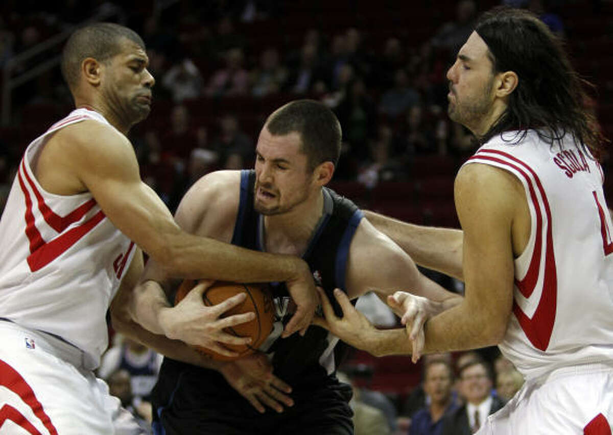 Rockets forwards Shane Battier, left, and Luis Scola, right, tangle with T-Wolves forward Kevin Love for a rebound.