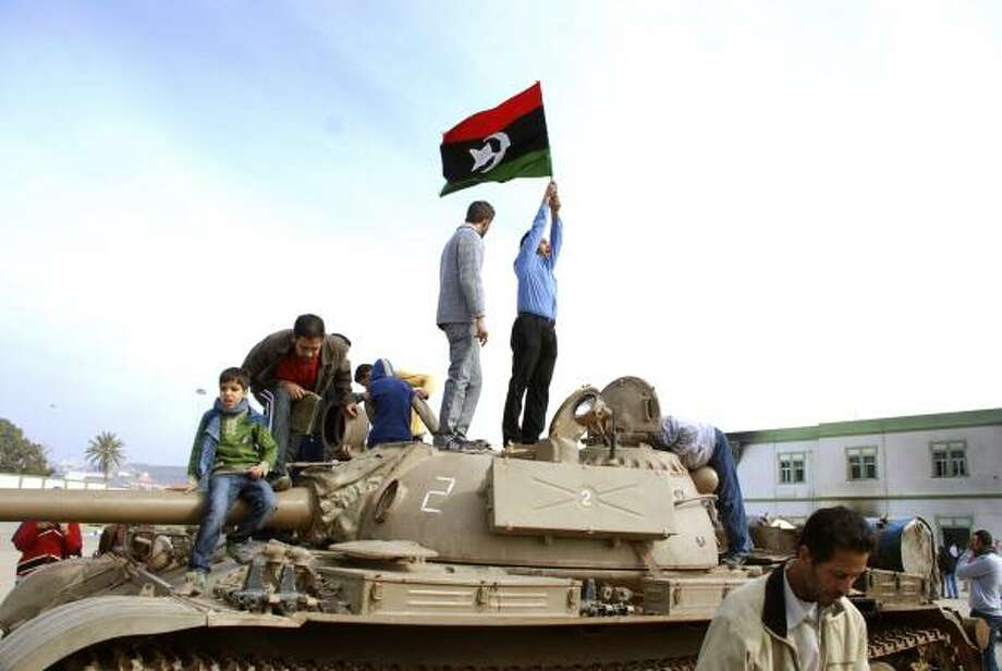 A protester waves an old national flag as others board a tank in Benghazi, Libya, the nation's second-largest city, on Monday. Protesters claimed control of the city after bloody fighting. Photo: ASSOCIATED PRESS