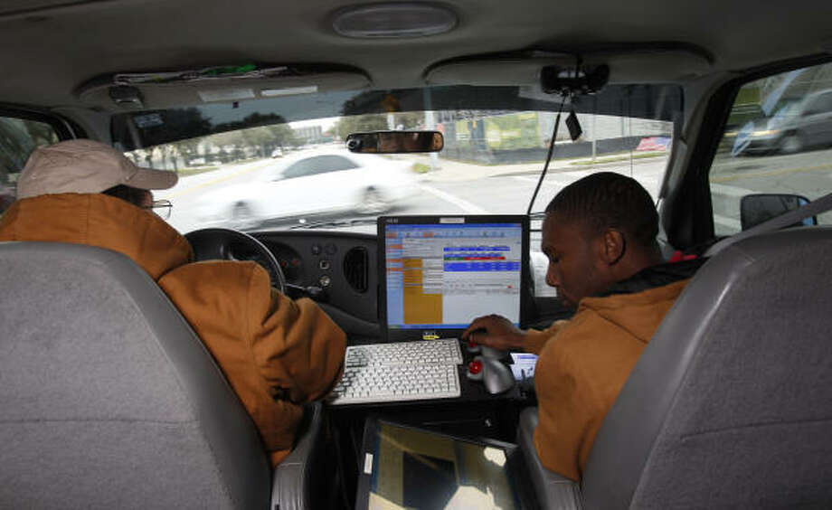 Bruno Rodriguez, left, and Patrick Johnson spend their days drawing stares and collecting data in the city's laser-equipped Houston Street Surface Assessment Vehicle. Photo: Melissa Phillip, Chronicle