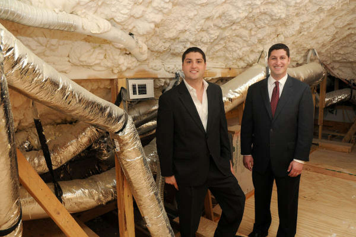 Scott Frankel, left, and Kevin Frankel show off the attic in an upscale green model home in ParkGate Reserve in The Woodlands.