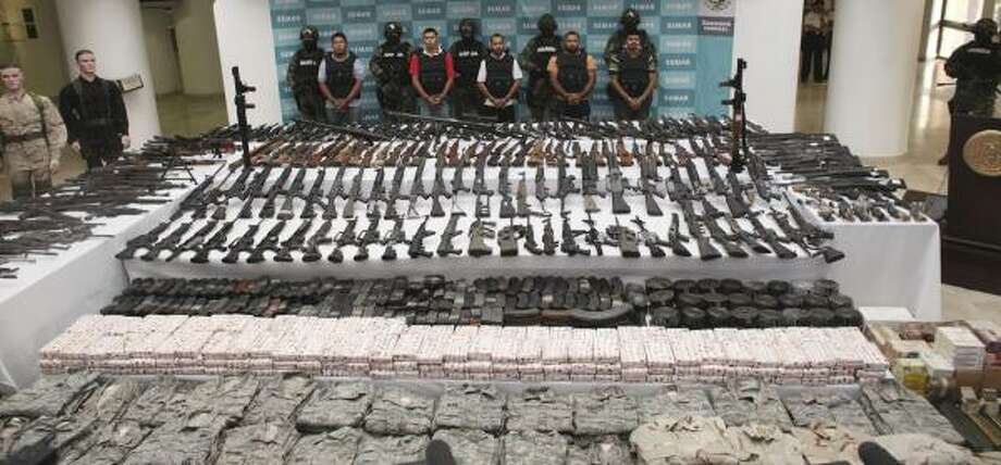 Soldiers escort five alleged members of the Zetas drug gang during their presentation to the press in Mexico City. Uniforms, ammunition and more than 200 weapons were seized after arresting the men at a Navy checkpoint, near Villa Union, in Mexico's Coahuila state. Photo: Alexandre Meneghini, Associated Press