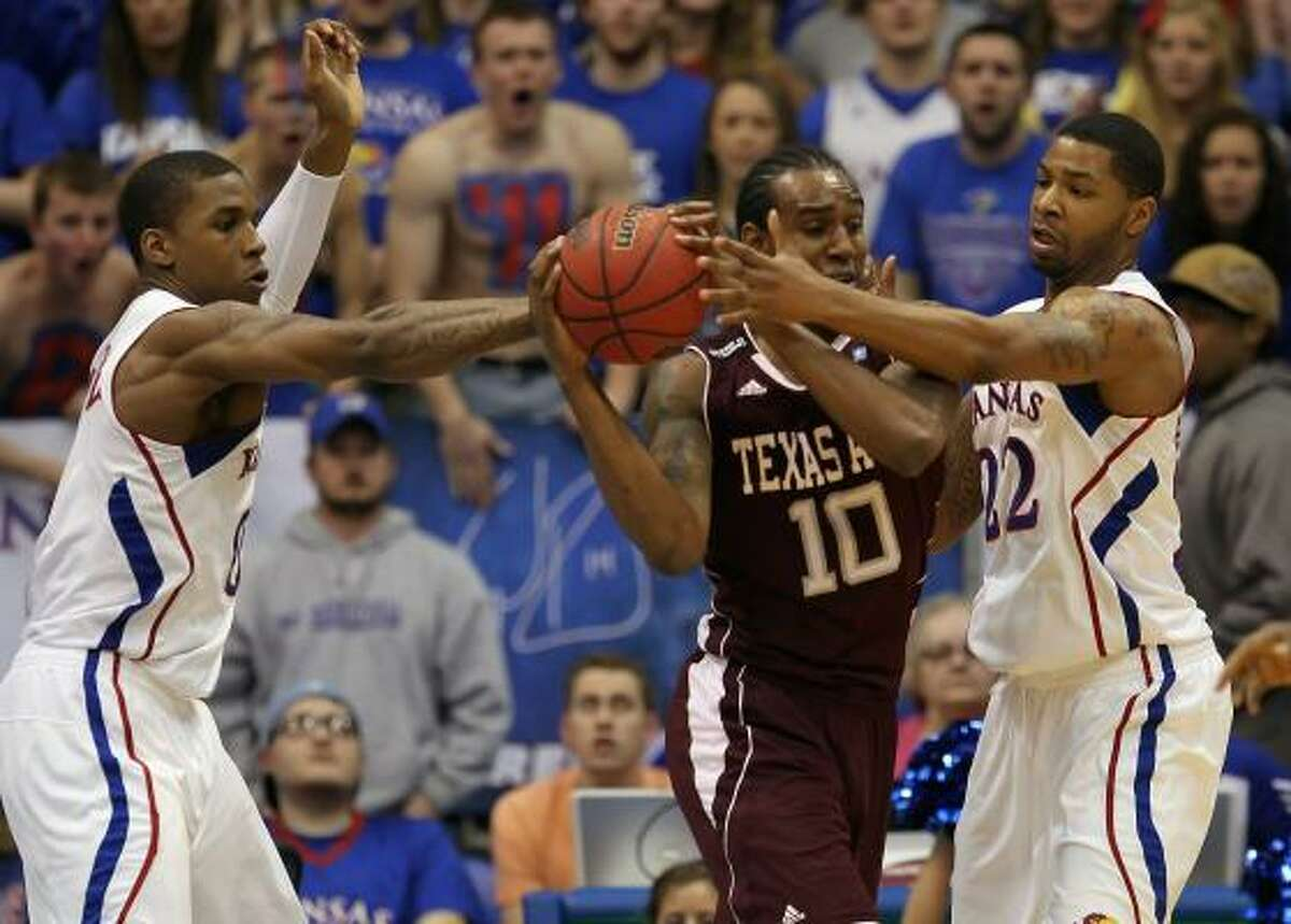 Texas A&M's David Loubeau tries to keep the ball away from Kansas' Thomas Robinson (0) and Marcus Morris (22).