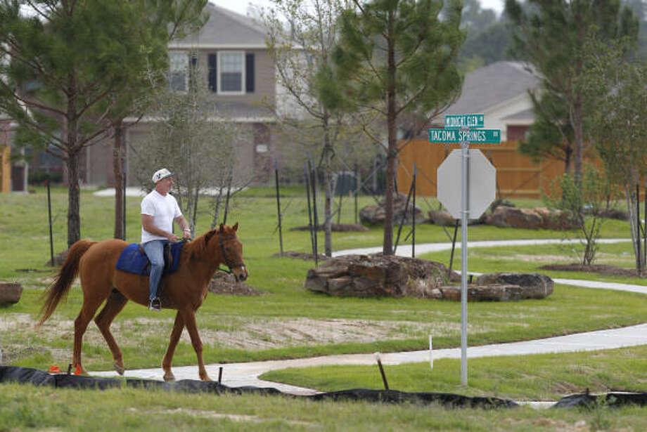 Allen VanDuyne rides his horse, Handsome Stuff, through a new subdivision in Northwest Harris County. Photo: Melissa Phillip, Houston Chronicle