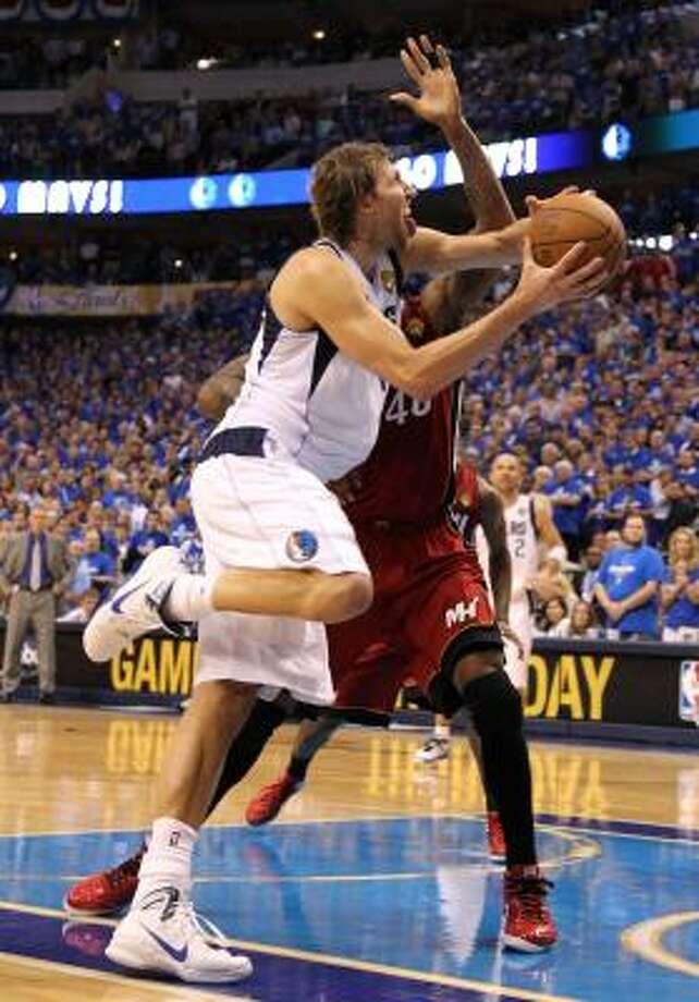 Dallas Mavericks forward Dirk Nowitzki goes up for a layup against Miami Heat forward Udonis Haslem 14 seconds remaining in the fourth quarter on Tuesday night. Photo: Mike Ehrmann, Getty