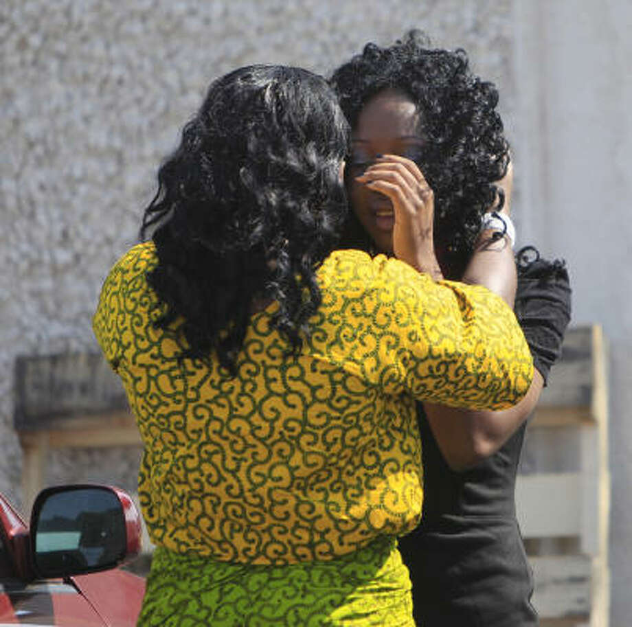 Kehinde Sule, left, embraces a choir member at the Christ Embassy Church. Photo: Mayra Beltran, Chronicle