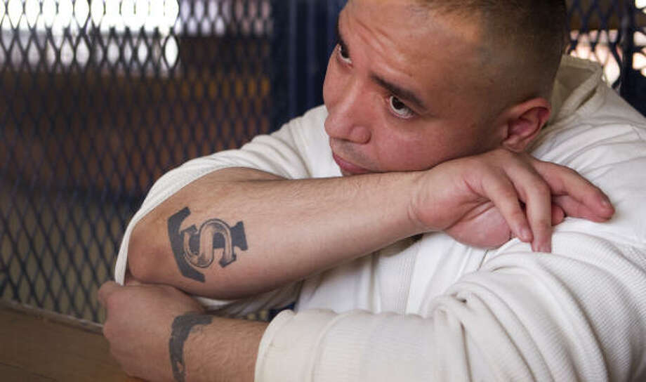 "Convicted killer Mike Mendoza Jr. shows his only ""free-world"" tattoo - ""TS"" for Texas Syndicate - in an interview. Photo: Brett Coomer, Chronicle"