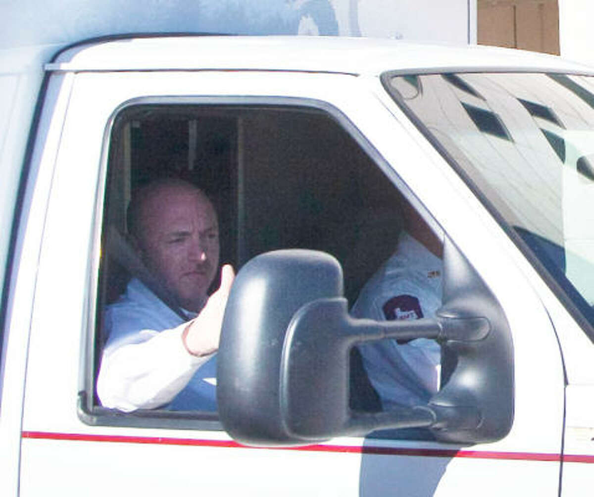 Astronaut Mark Kelly waves to the media as he sits in an ambulance carrying Congresswoman Gabrielle Giffords as she leaves Memorial Hermann to be transported to TIRR, Wednesday, Jan. 26, 2011, in Houston.