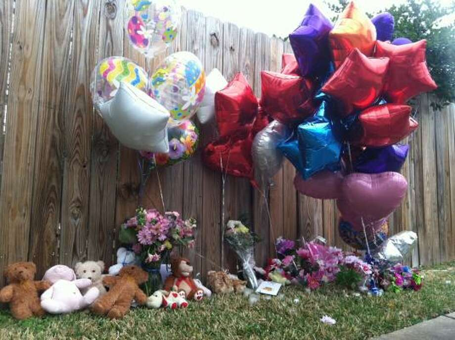 "A makeshift memorial lines a fence Saturday near where the fatal day care fire occurred. One witness said he tried to crawl inside the house and ""could hear children screaming from everywhere,"" but he became overwhelmed by smoke and had to retreat. Photo: Mike Morris, Chronicle"