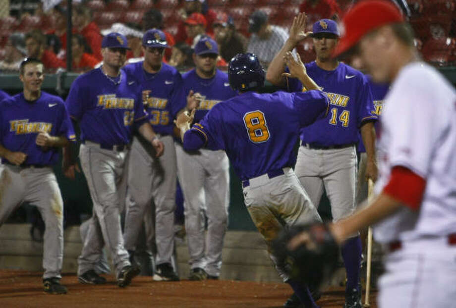 East Carolina's Jack Reinheimer crosses the plate to score the winning run as UH pitcher Chase Wellbrock walks off the field. Photo: Michael Paulsen, Chronicle