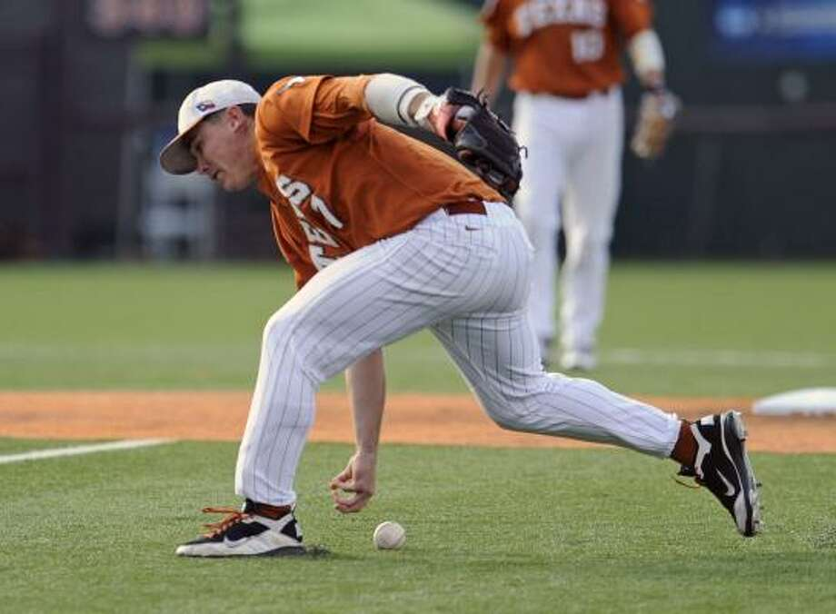 Texas second baseman Jordan Etier tries to barehand a groundball during the first inning on Friday night. Photo: Michael Thomas, Associated Press