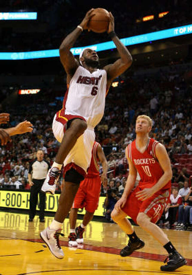 Rockets forward Chase Budinger, right, looks on as Heat forward LeBron James takes the ball to the basket. James scored a game-high 33 points. Photo: Marc Serota, Getty Images