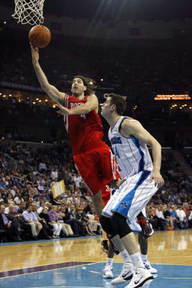 Rockets power forward Luis Scola drives to the basket against Hornets power forward Jason Smith. Photo: Gerald Herbert, AP