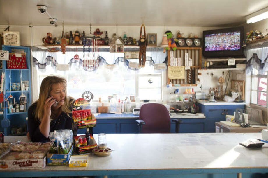 """PHOTOS: The least-populated county in TexasCaren Calloway talks to a friend on her cell phone while running the register at the only store in Mentone, Texas, which is a small gas station. Calloway, who grew up in Pecos, said she moved to Loving County from Odessa after being divorced. """"You can always come back home"""", Calloway said.Click through to see more images from Texas' least populous county... Photo: Albert Cesare, For The Chronicle"""