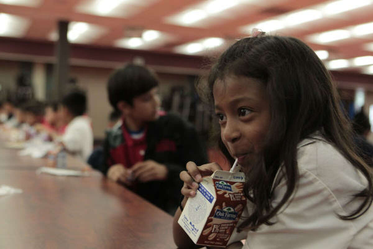 Kindergartner Alondra Landeros takes a sip of milk at Youens Elementary in Houston. The census shows that key urban areas in Texas are younger, mostly due to the Hispanic population.
