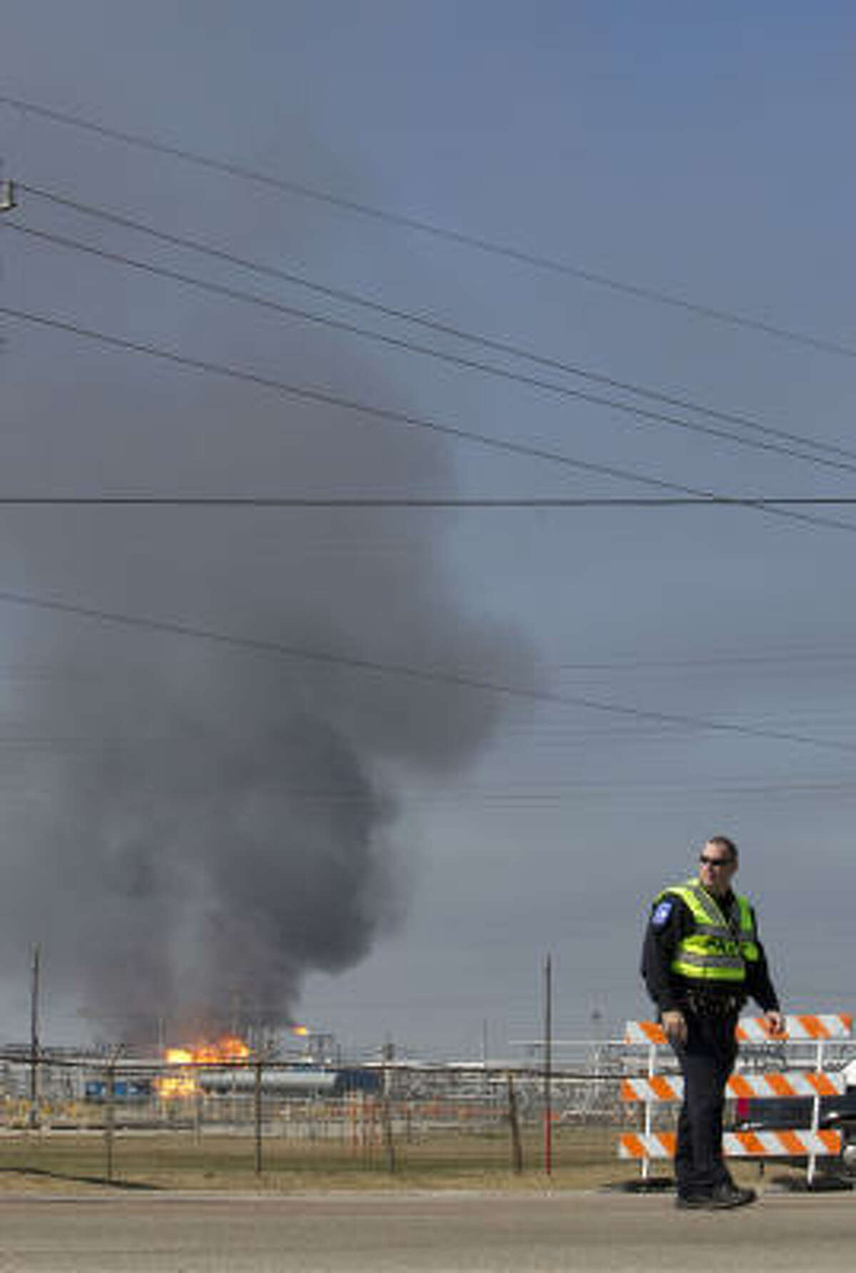 A Baytown police officer diverts the flow of traffic at Sun Oil Rd and Main, Tuesday, February 8, 2011 as flames and smoke rise from an explosion at Enterprise Products in Mont Belvieu.