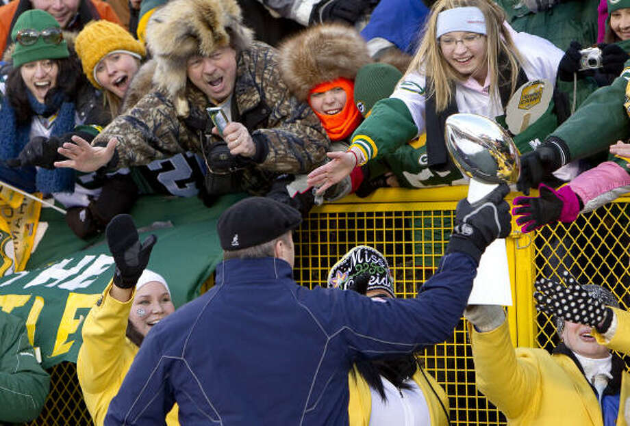 "Fans try to touch the Vince Lombardi trophy as Packers head coach Mike McCarthy holds it as he walks past them during the ""Return to Titletown"" celebration. Photo: Mike Roemer, AP"