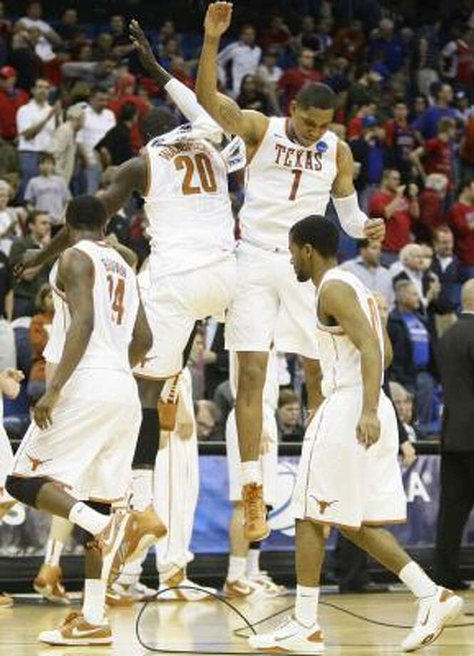 Texas' Alexis Wangmene (20) and Gary Johnson (1) celebrate after the win over Oakland. Photo: Nick De La Torre, Chronicle