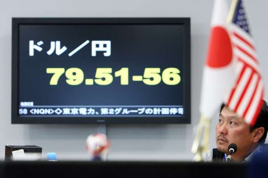 A currency trader works under a monitor displaying the exchange rate of the yen against the dollar at a Tokyo brokerage. The yen jumped 4.5 percent in 26 minutes. Photo: Tomohiro Ohsumi:, Bloomberg