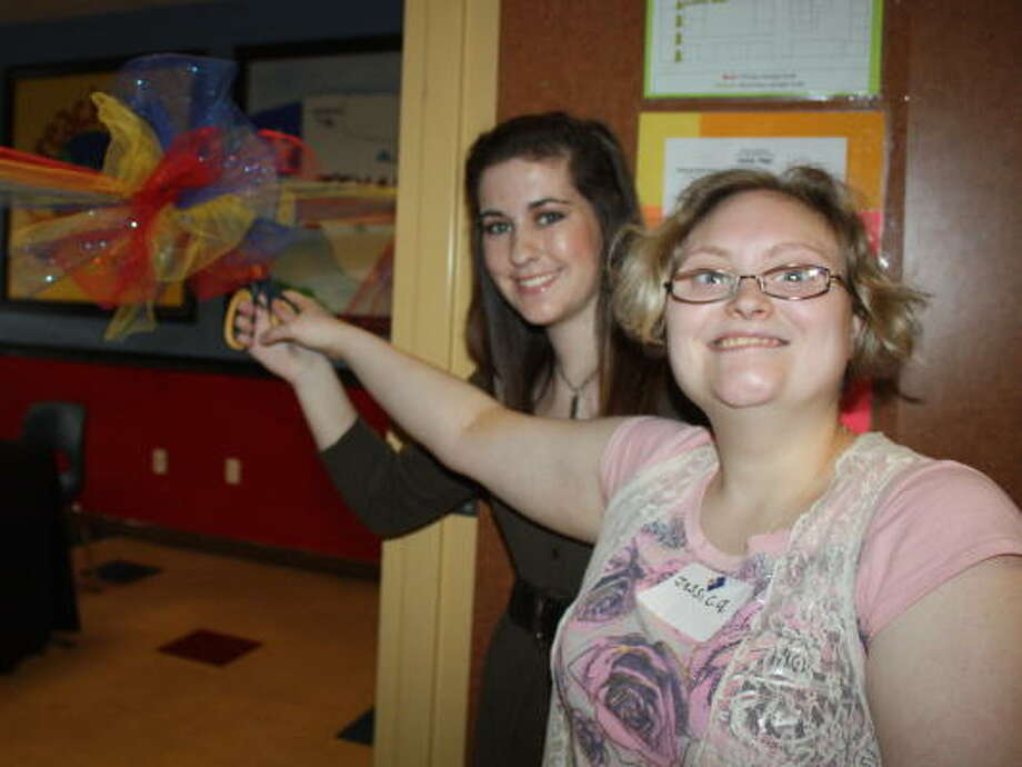 GRAND OPENING: Reach Unlimited Learning Activity Center client Jessica Cranford, right, joined Girl Scout Brittany Adrian to cut the ribbon on the Reach 2 You Newsroom, which was a project organized by Adrian to earn an award. BARBARA SCHNEIDER: REACH UNLIMITED PHOTO