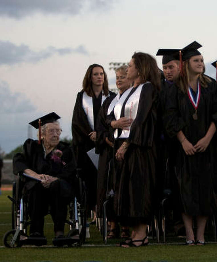 Thelma Dyess, 100, shown with other graduates who are more than eight decades younger than she is, waits to receive her honorary diploma during graduation ceremonies for Texas City High School on Friday. Photo: Johnny Hanson, Chronicle